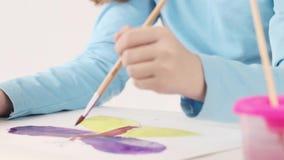 Handen van meisjeswaterverf het schilderen vlinder stock video