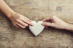 Handen van mens en vrouw door een hart wordt de verbonden dat Royalty-vrije Stock Afbeelding
