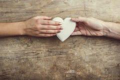 Handen van mens en vrouw door een hart wordt de verbonden dat Royalty-vrije Stock Foto