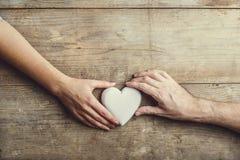 Handen van mens en vrouw door een hart wordt de verbonden dat Stock Foto's