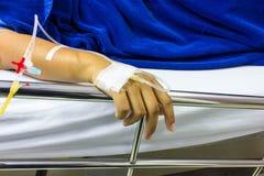 Handen van mensen zieke gehouden van degenen die op een bed in het ziekenhuis liggen Stock Foto's