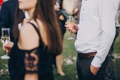Handen van modieuze mensen die met glazen champagne, luxu toejuichen stock fotografie