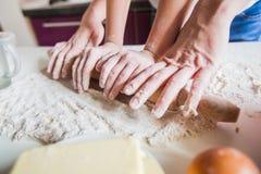 Handen van Moeder en Dochter Rolling Pizzadeeg met Deegrol stock foto