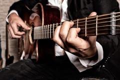 Handen van musicus die de gitaar spelen stock afbeelding