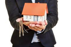 Handen van onroerende goederenmakelaar met huis en sleutels stock foto's