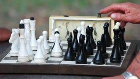 Handen van oude mensen die schaak in park spelen stock footage