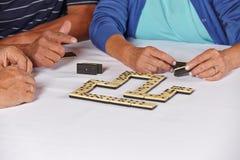 Handen van oudsten die domino spelen Stock Foto's