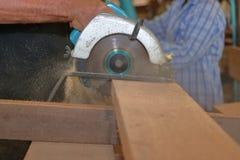 Handen van professionele timmerman die cirkelzaag gebruiken die houten raad in houten workshop snijden stock afbeelding
