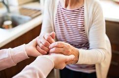 Handen van tiener en haar grootmoeder thuis stock afbeeldingen