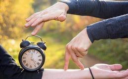 Handen van twee vrouwen en een zwart uitstekend horloge De tijd van de fotoabstractie stock foto