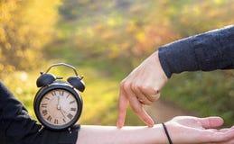 Handen van twee vrouwen en een zwart uitstekend horloge De tijd van de fotoabstractie royalty-vrije stock foto