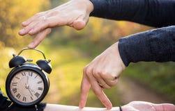 Handen van twee vrouwen en een zwart uitstekend horloge De tijd van de fotoabstractie royalty-vrije stock afbeelding
