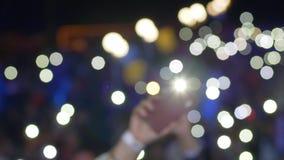 Handen van ventilators met smartphone met het branden van lantaarns die bij rotsoverleg golven stock videobeelden