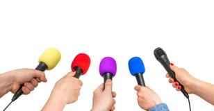 Handen van verslaggevers met vele die microfoons op wit worden geïsoleerd Stock Afbeeldingen