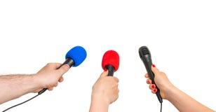 Handen van verslaggevers met vele die microfoons op wit worden geïsoleerd Stock Foto