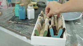 Handen van vingertechniek de kruik en flessen die van verf, de juiste kleur in de vazen de plukken stock footage