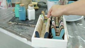 Handen van vingertechniek de kruik en flessen die van verf, de juiste kleur in de vazen de plukken stock video