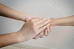 Handen van vrouw die de hand van een jongere vrouw houden royalty-vrije stock afbeeldingen