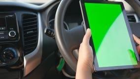 Handen van vrouw die gebruikend tablet met groene het schermmonitor bij binnenland van SUV-auto voor mobiele toepassingstechnolog stock footage