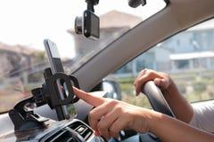Handen van vrouw die mobiele slimme telefoon in de auto voor mobiele te met behulp van Royalty-vrije Stock Foto's