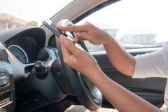 Handen van vrouw die mobiele slimme telefoon in de auto voor mobiele te met behulp van Royalty-vrije Stock Foto