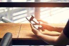 Handen van vrouw die mobiele smartphon op houten lijst gebruiken stock afbeelding