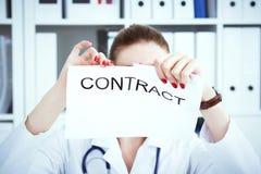Handen van vrouwelijk geneeskunde artsen scheurend contract Foto met diepte van gebied stock foto