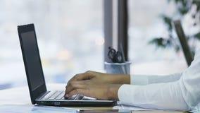 Handen van vrouwelijke secretaresse het schrijven nota's met pen en het typen bericht op laptop stock videobeelden