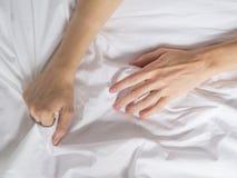 Handen van vrouwen die witte bladen in verlangen en orgasme trekken stock foto