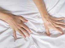 Handen van vrouwen die witte bladen in verlangen en orgasme trekken stock afbeelding