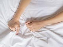 Handen van vrouwen die witte bladen in verlangen en orgasme trekken royalty-vrije stock afbeeldingen