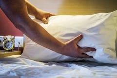 Handen verbeterd hoofdkussen op het bed royalty-vrije stock afbeelding