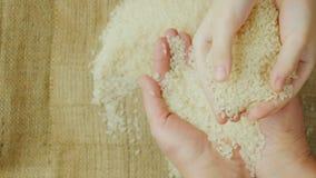 Handen volwassen vrouw die een korrel van rijst, over hen houden als kinderen` s handen die rijst houden stock videobeelden