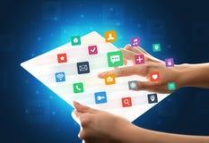 Handen wat betreft een glass-like tablet met kleurrijke pictogrammen Stock Foto's