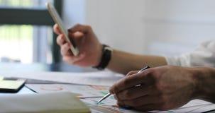 Handenclose-up die van jonge zakenmanzitting bij de lijst in bureau, gegevens analyseren en smartphone gebruiken collagues stock video