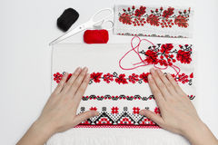 Handenmeisjes die op een handdoek met geborduurd traditioneel Oekraïens patroon liggen Stock Afbeelding