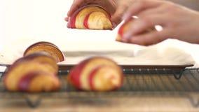 Handenoverdracht gebakken croissants aan een rooster stock video