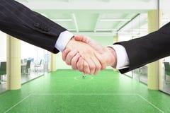 Handenschudden van partners bij backgro van het bureau footbal gebied Stock Afbeelding