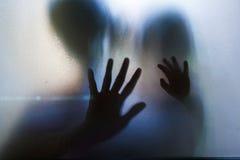 Handensilhouet achter glasdeur Stock Afbeelding