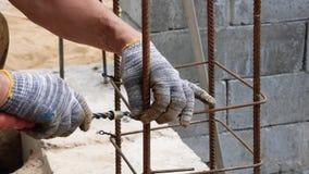 Handerbauer In Dirty Gloves band Stahldraht auf Rebar-Werkzeug auf Baustelle stock video