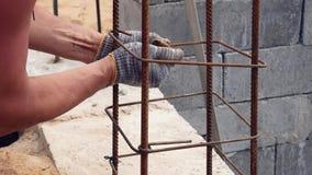 Handerbauer In Dirty Gloves band Stahldraht auf Rebar-Werkzeug auf Baustelle stock video footage