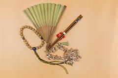 Handfans, Essstäbchen, buddhistische Gebetsperlen, Oberteile auf einem beige Hintergrund stockfotografie