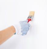 Handfarbtonwand mit Malerpinsel stockfotos