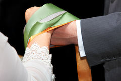 Handfasting wedding ceremony. Handfasting / hand tying wedding ceremony.  Bride and groom joined by ribbons Stock Image