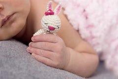 Handfinger eines neugeborenen Babys, Häschenspielzeug in der Hand, Nägel eines Kindes, die ersten Tage des Lebens nach Geburt, sc stockbilder