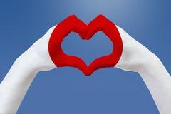 Handflaggan av Japan, formar en hjärta Begrepp av landssymbolet, på blå himmel Arkivbilder