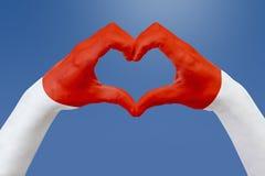 Handflaggan av Monaco, formar en hjärta Begrepp av landssymbolet, på blå himmel Arkivbild