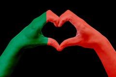 Handflaggan av Portugal, formar en hjärta Begrepp av landssymbolet som isoleras på svart Royaltyfri Bild