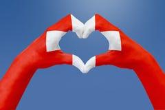 Handflaggan av Schweiz, formar en hjärta Begrepp av landssymbolet, på blå himmel Royaltyfri Fotografi