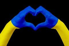 Handflaggan av Ukraina, formar en hjärta Begrepp av landssymbolet som isoleras på svart Royaltyfri Foto